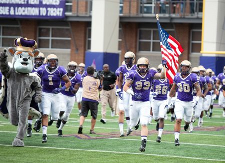 (9/13/14) - (Harrisonburg) ------- Saint Francis vs James Madison football------- JMU linebacker Gage Steele holds the colors as he leads the Dukes into Bridgeforth Stadium/Zane Showker Field Saturday with the Duke Dog for the first home game of the season. Saint Francis fell to the Dukes 38-22. (Michael Reilly/Daily News-Record)